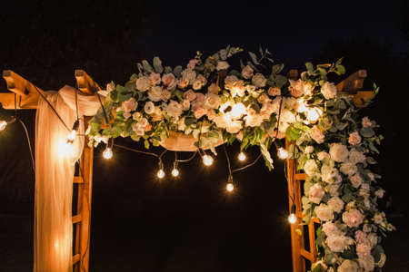 Foto de Beautiful place made with wooden square and floral decorations for outside wedding ceremony in night wood. Horizontal color photography. - Imagen libre de derechos