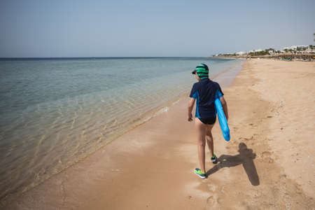 Photo pour Cute white tanned kid dressed in swimsuit, cap and aqua shoes having fun at summer sandy beach using blue inflatable surf board. Boy walking alone with his back to camera. Horizontal color photography - image libre de droit