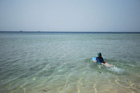 Photo pour Cute white tanned kid dressed in swimsuit, cap and aqua shoes having fun at summer sandy beach using blue inflatable surf board. Horizontal color photography. - image libre de droit