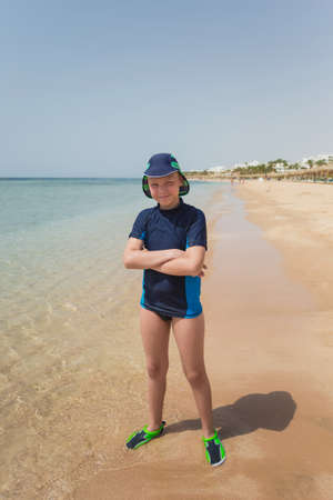 Photo pour Portrait of happy smiling young caucasian tanned kid standing on sunny sandy beach in Egypt. Vertical color photo of boy in full length. Child wearing special swimwear for protection from sunlight. - image libre de droit
