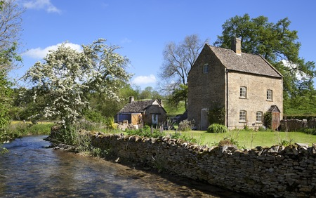 Pretty cottage on the banks of the River Dikler, Gloucestershire, England