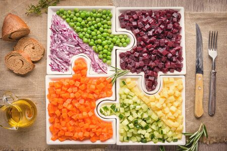 Photo for  Delicious fresh pieces of vegetables of carrots, cucumber, potatoes, beets and peas close-up with fresh onion and olive oil on a bag cloth on a rustic gray table. - Royalty Free Image