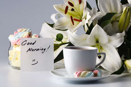 Breakfast concept. Cup of tea, white lily and note good morning