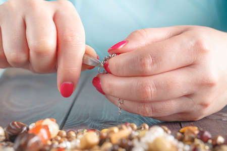 Woman make handmade beads. Leisure concept