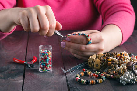 Relax hobby. Female make craft beads