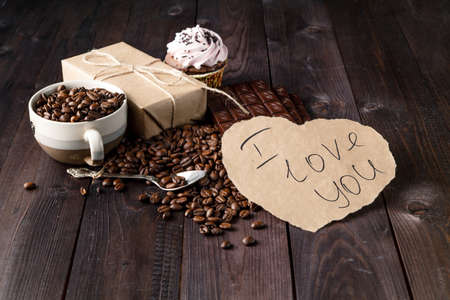 Love message on table with roasted coffee beans and stack of brown chocolate on dark table