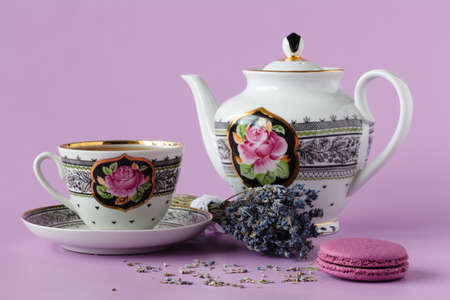 Purple heather with antique porcelain tea cup with saucer and tea, lavender tea, sunny day, daylight