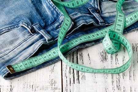 Measuring tape and jeans with wooden background