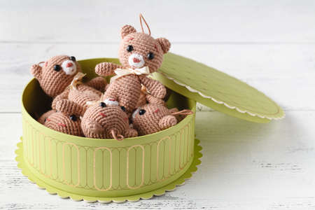 Toy knitted bear with gigt box on table