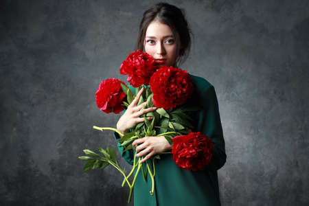 Photo for Beautiful girl in tender green dress with bouquet flowers peonies in hands. Playful fashion model looking at camera - Royalty Free Image