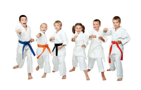 Young children in kimono perform techniques karate on a white background