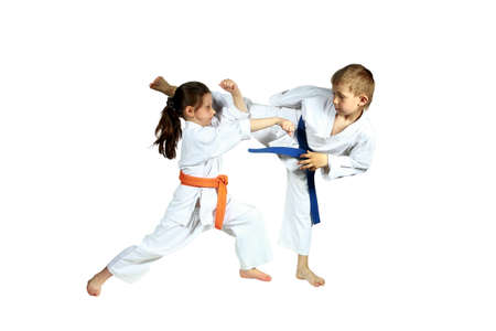 Girl and boy in karategi are training paired exercises karate