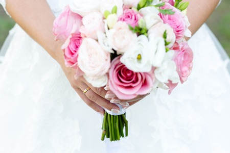Photo pour Wedding bouquet of roses and freesias in the hands of the bride - image libre de droit