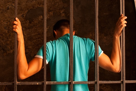 Photo for Man with hands tied with rope behind the bars - Royalty Free Image