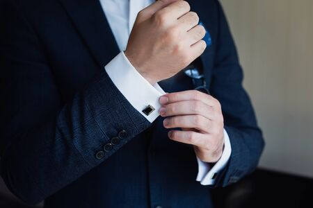 Photo pour Close-up of a man in a tux fixing his cufflink. - image libre de droit