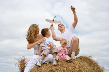 Happy family launching toy aircraft model sitting on haystack together