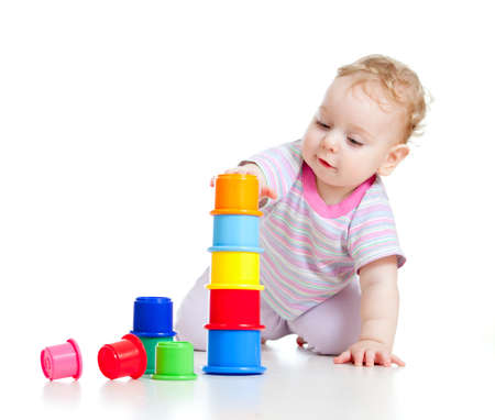 Cute little boy building tower from colorful cups isolated on white
