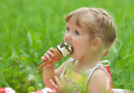 Photo pour little girl eating ice cream outdoor - image libre de droit