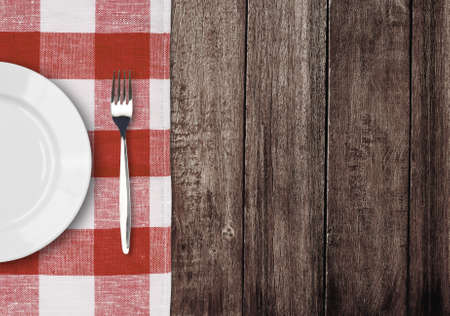 white plate and fork on old wooden table with red checked tablecloth and copyspace