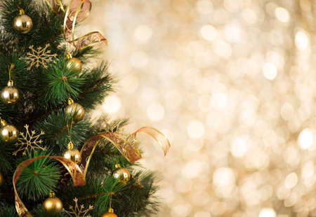 Gold Christmas background of defocused lights with decorated tree