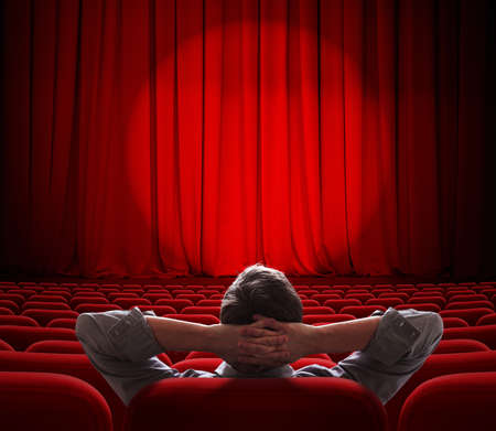 man sitting alone in  empty theater or cinema hall