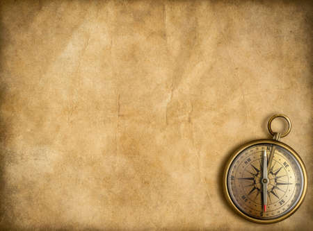 old golden compass with vintage map background