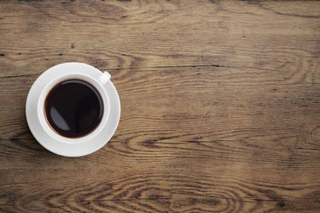 Black coffee cup on old wooden table
