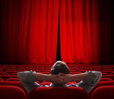 cinema screen red curtains slightly open for vip person