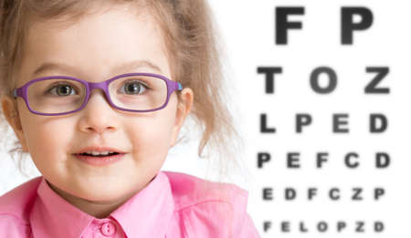 Photo pour Smiling girl putting on glasses with blurry eye chart behind her isolated on white - image libre de droit