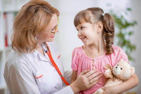 Pediatrician doctor talking with kid kindly
