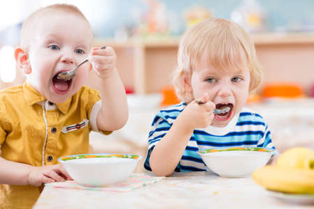 Photo for funny kids eating in kindergarten - Royalty Free Image