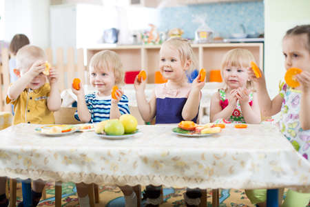 Funny kids eating fruits in day care centre