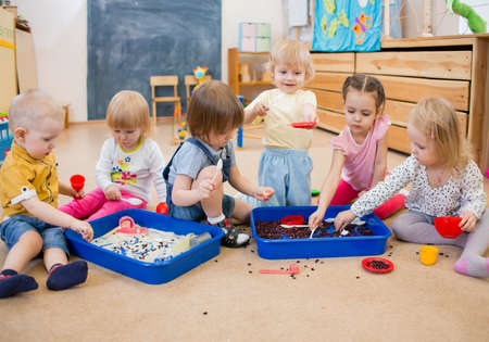 Foto de Group of children playing with rice and beans in kindergarten or day care centre - Imagen libre de derechos