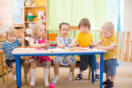 Photo pour kids group learning arts and crafts in day care centre playroom - image libre de droit
