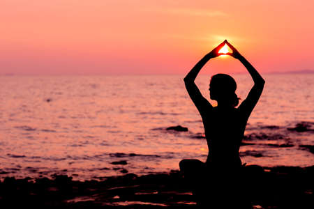 Photo pour Woman silhouette sitting in lotus position on sunset sea background back lit - image libre de droit