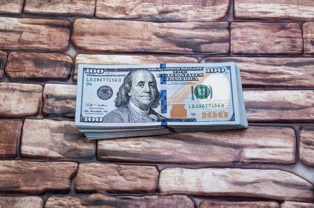 Dollars cash bills on a brick background