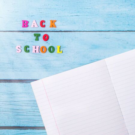 Photo for Layout of school supplies on a blue wooden background. Top view, sun rays from the side. Flat lay - Royalty Free Image