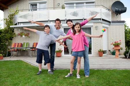 Photo for Portrait of happy young family enjoying themselves outside their new home - Royalty Free Image