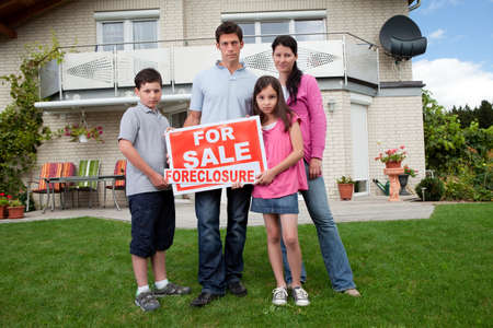 Portrait of young family holding a foreclosure sign outside their houseの写真素材