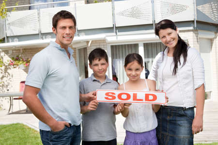 Smiling young family with a sold sign standing outside their new house