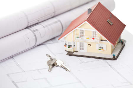 Model home and house key on architectural floor plans