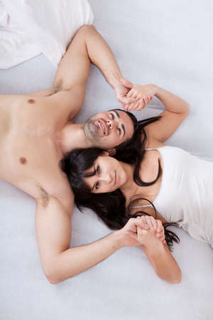 Happy young couple lying up in bed