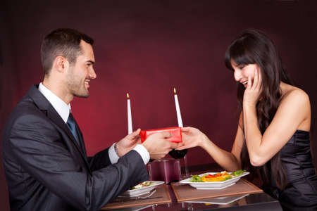 Photo pour Man giving present to a woman at romantic dinner in restaurant - image libre de droit