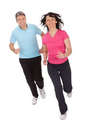 Mature fitness couple running towards camera. Isolated on whiteの写真素材