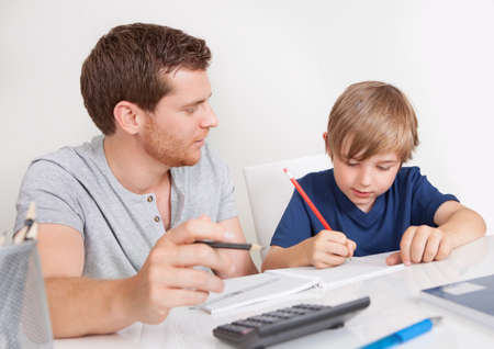 Young boy doing homework together with his father
