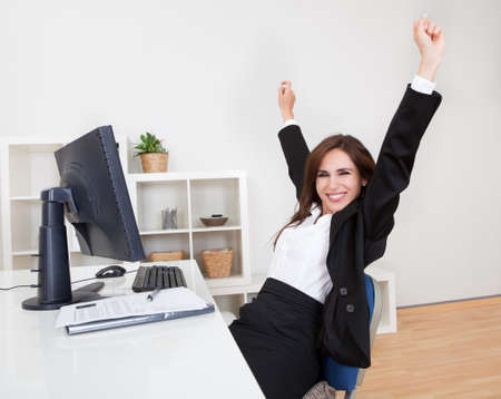Portrait of Cheering Businesswoman At Desk In Office.