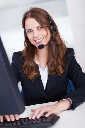 Smiling receptionist or call centre worker sitting typing at a computer while speaking into a headset with a microphone