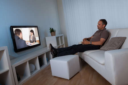 Man recline comfortably on his living room couch watching home movies on his widescreen television set