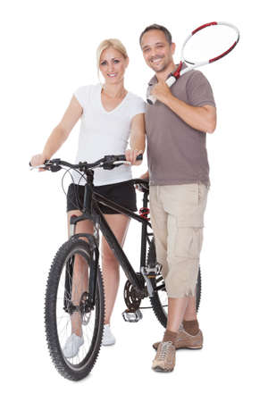 Fit healthy middle-aged parents who enjoy an active outdoor lifestyle standing with a tennis racquet and bicycle