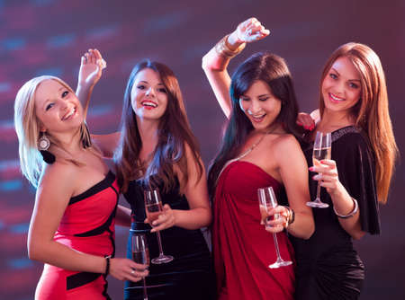 Group of four stylish women standing in a row toasting with flutes of champagne